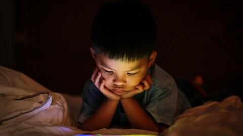 Un enfant regarde une tablette dans son lit le soir.