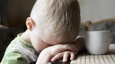 Un enfant a le front appuyé sur ses mains pendant qu'il est assis à une table.