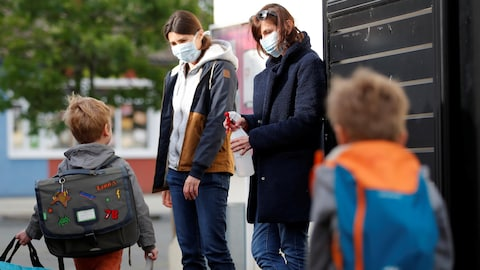 Deux enseignantes portant des masques sur le visage sont à l'extérieur d'une école et deux jeunes garçons se dirigent vers elles avec leurs sacs d'école. Une des deux femmes a une bouteille de désinfectant à la main.
