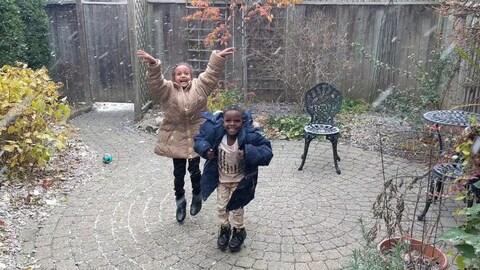 Deux jeunes enfants qui dansent dans la neige