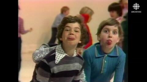 Deux garçons d'environ 10 ans font des grimaces à la caméra.