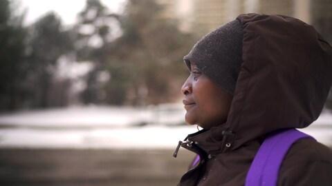 Caroline avec son manteau d'hiver marron et son bonnet gris. Elle porte un sac à dos mauve.