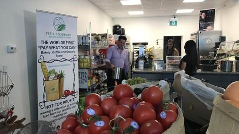 Trois personnes se tiennent dans une épicerie. Des tomates sont au premier plan.