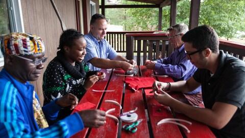 Les 5 personnes sont assises autour d'une table avec le matériel pour fabriquer les sacs
