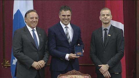 Trois hommes sourient à la photographe. Derrière, il y a un drapeau du Québec et du Canada.