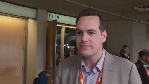 Le député Erin Weir interrogé à l'extérieur d'une salle de conférence
