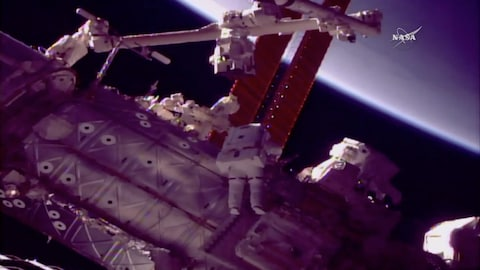 Deux astronautes travaillent à réparer le bras canadien de la Station spatiale internationale.