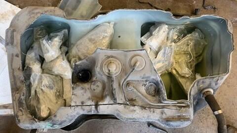 Un réservoir à essence ouvert avec des sacs de plastique dedans.