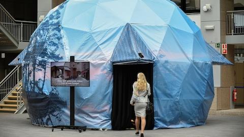 Une femme entre dans une tente en forme d'igloo, haute de quelques mètres.