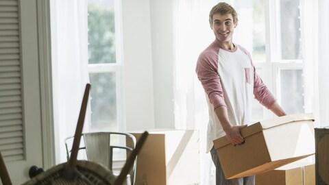 Un jeune homme souriant transporte une boîte de carton.