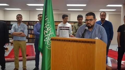 Un homme aux lunettes rectangulaires parle au micro. Au second plan, à sa droite, deux hommes bruns et le drapeau de l'Arabie saoudite.