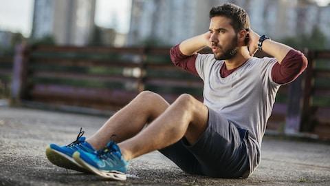 Un homme réalise des redressements assis.
