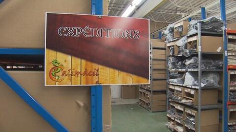 """Une affiche sur laquelle il est inscrit """"expéditions"""" et """"colimacil"""" est accrochée à des étagères en métal bleu."""