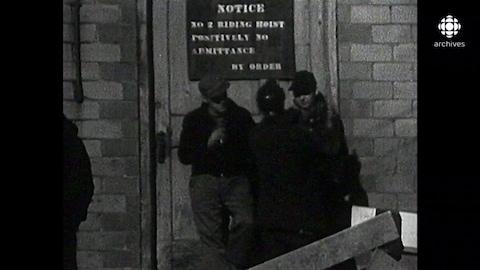 Des mineurs se tiennent debout devant l'entrée de la mine, qui est interdite d'accès.