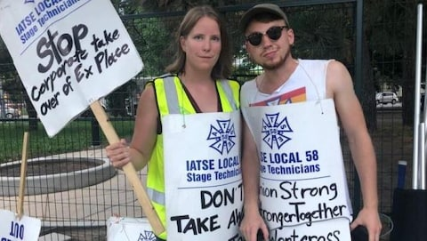 Une femme avec une pancarte à la main et un homme à ses côtés.