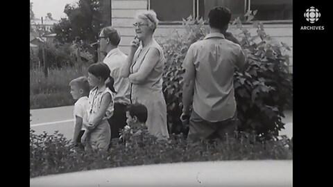 Famille de Sainte-Scholastique qui regarde les maisons quitter leur village.
