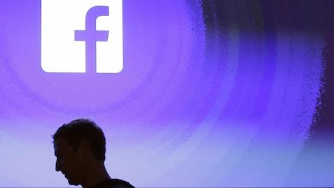 Mark Zuckerberg, de profil, devant le logo de son entreprise Facebook