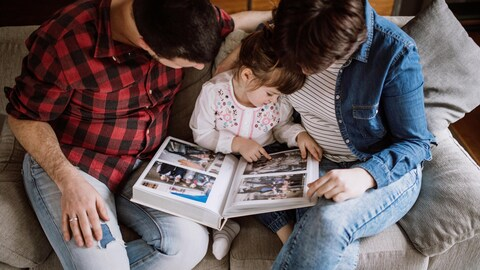 Une famille regarde un album de photos.