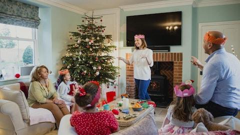 Une famille est réunie dans le salon de la maison. La mère est debout et explique les règles du jeu aux enfants et aux grands-parents.