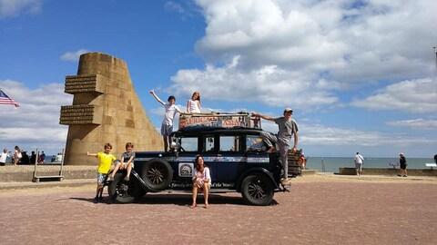 Une famille - une mère, un père et quatre enfants - posent autour d'une vieille voiture devant un monument sur une plage du débarquement en Normandie.