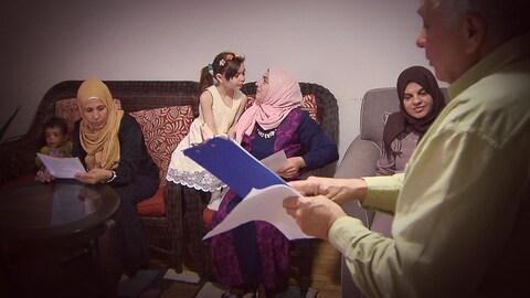 Un homme tiens des documents en main, trois femmes sont assises sur un canapé et elles l'écoutent parler