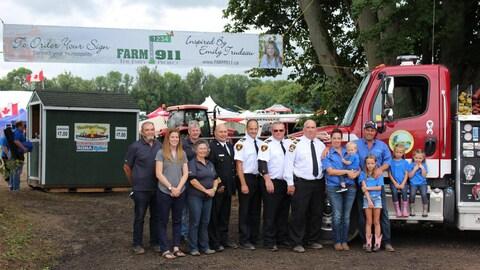 Des citoyens et des policiers sont devant un camion durant une exposition agricole.