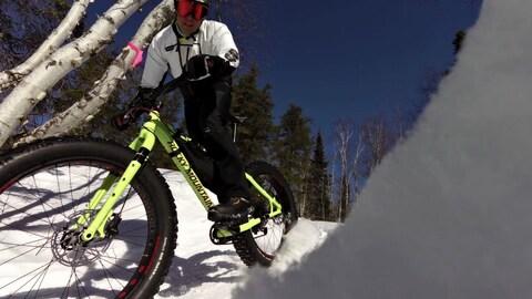 Un homme passe au-dessus de la caméra au guidon d'un vélo à pneus surdimensionnés.