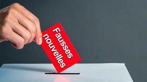 Une personne dépose un bulletin de vote sur lequel il est écrit «fausses nouvelles» dans une urne.
