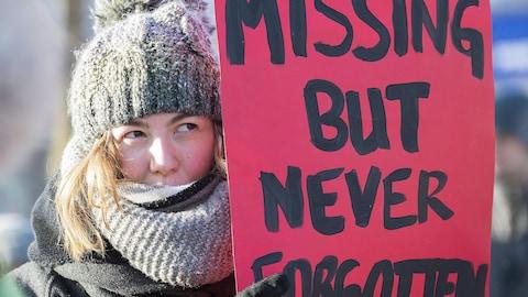 « Disparue mais pas oubliée » peut-on lire sur la pancarte d'une participante à une marche commémorative