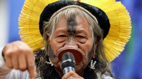 Une leader autochtone s'adressant au sénat brésilien à l'aide d'un micro.