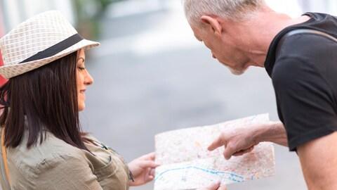 Sur la rue, une femme demande à un homme de lui indiquer une direction.