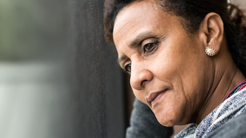 Une femme pensive regarde par la fenêtre.