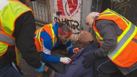 Trois personnes vêtues de dossards oranges et jaunes interviennent auprès d'un homme en état de surdose.