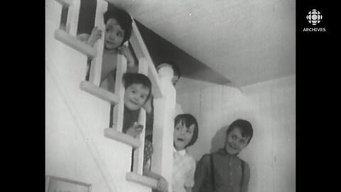 Des enfants posent dans les escaliers d'une ferme familiale.
