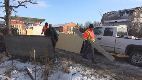 Des ouvriers démantèlent une clôture improvisée sur une ferme délabrée.