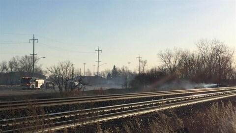 Des pompiers éteignent un feu près de la voie ferrée.