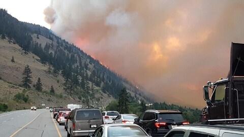 Des voitures sur une route avec un feu de forêt dans l'arrière-plan.