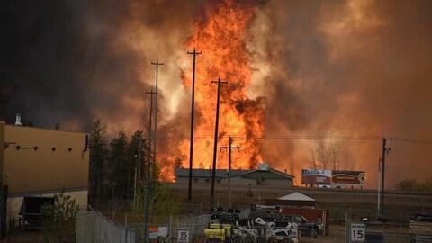 Des flammes montent jusqu'au ciel devant une maison et ce qui ressemble à une zone industrielle.