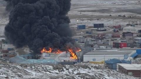 Vue au loin d'un épais panache de fumée qui s'échappe d'un grand incendie du magasin Northmart d'Iqaluit.
