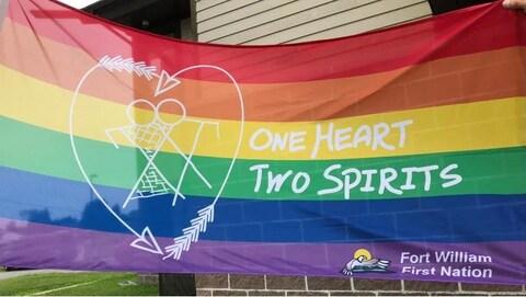 Un drapeau multicolore un homme et une femme dans un cœur avec deux flèches