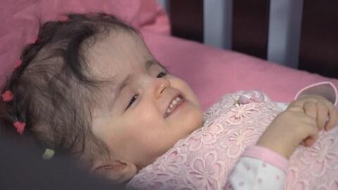 On voit la petite fille couchée sur un lit. Elle sourit.