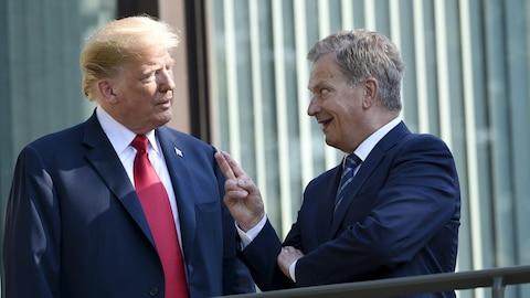 Deux hommes en complet discutent sur le balcon d'un immeuble. L'un d'eux pointe deux doigts vers le ciel en souriant.