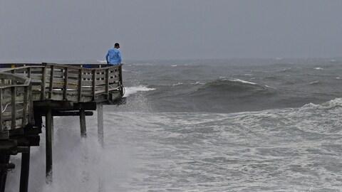 Des vagues se cassent sur la structure d'un quai en Caroline du Nord.