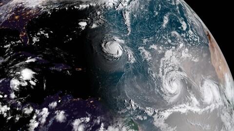 Vue sur l'océan Atlantique de l'espace où l'on voit la formation de nuages en spirale propres aux ouragans à trois endroits distincts, soit les tempêtes tropicales Florence, Isaac et Helene.