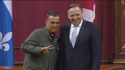Deux hommes sourient, l'un d'eux lève deux doigts pour faire le signe de la paix.
