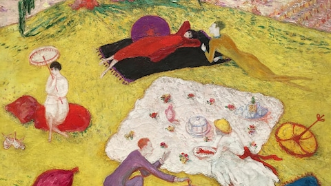 Scène de pique-nique avec de grandes couvertures sur l'herbe jaune. Deux hommes et trois femmes.