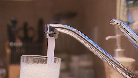 Un robinet qui laisse couler de l'eau dans un verre.