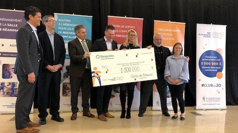 Des responsables de la Fondation tiennent un énorme chèque d'un million de dollars.