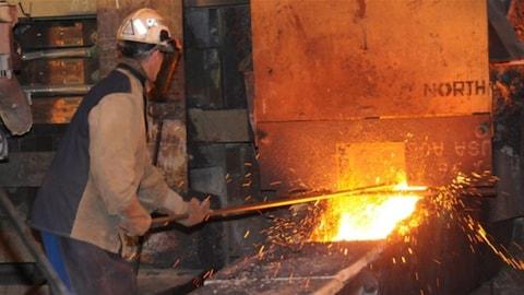 Un travailleur en train de fondre du métal.