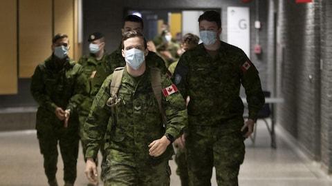 Des militaires des forces armées canadiennes portant un masque dans un couloir d'un collège.